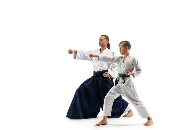 Man and teen boy fighting at aikido training in martial arts school. healthy lifestyle and sports concept. fightrers in white kimono on white wall. karate men with concentrated faces in uniform. Free Photo