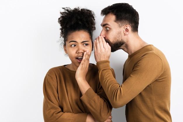 Man telling woman a secret Free Photo