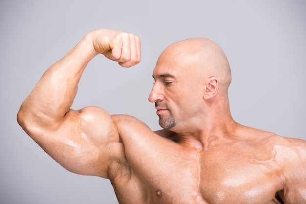 Man tensed his biceps muscle and looks at her. Premium Photo