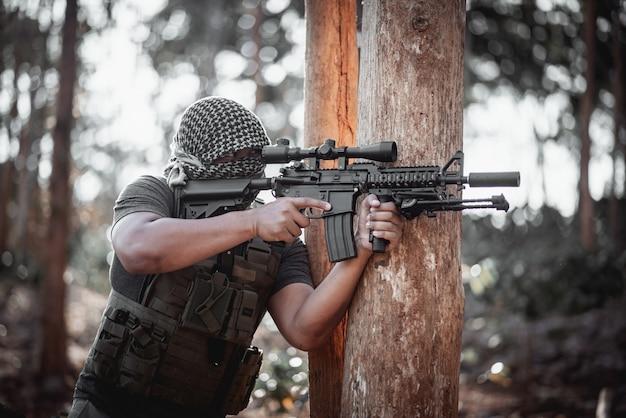 Man terrorist wearing a mask and holding a gun, terrorist concpet Premium Photo