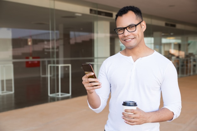 Man texting on phone, holding takeaway coffee, looking at camera Free Photo