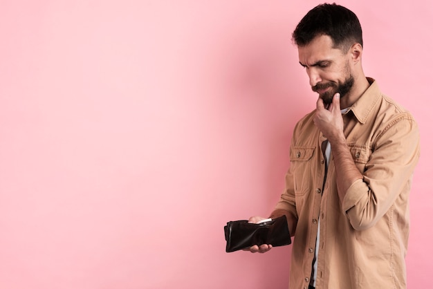 Man thinking while holding empty wallet Free Photo