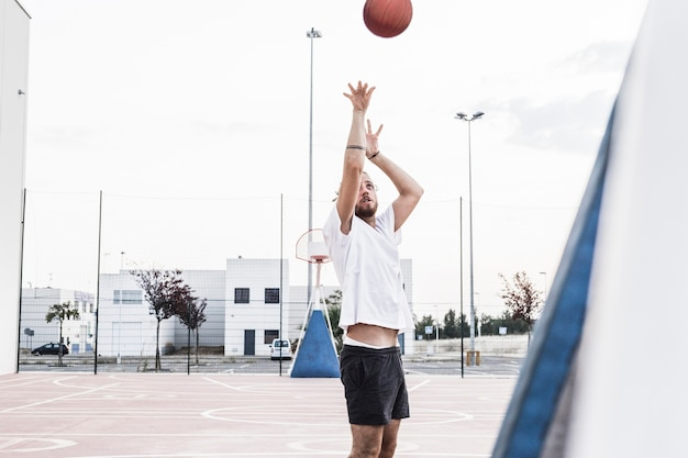 Man throwing basketball in mid-air Free Photo