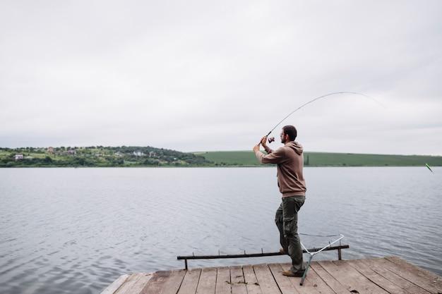 Man throwing fishing line in the lake Free Photo