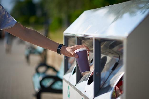 Man throwing paper coffee cup in waste sorting bin Premium Photo