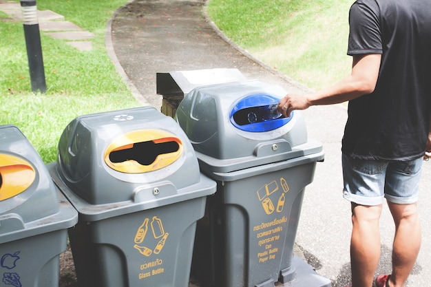 Man throwing plastic bottle in recycle trash can Free Photo