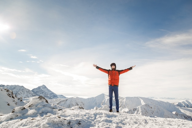 Man on the top of the world raised his hands proud of his achievements Premium Photo