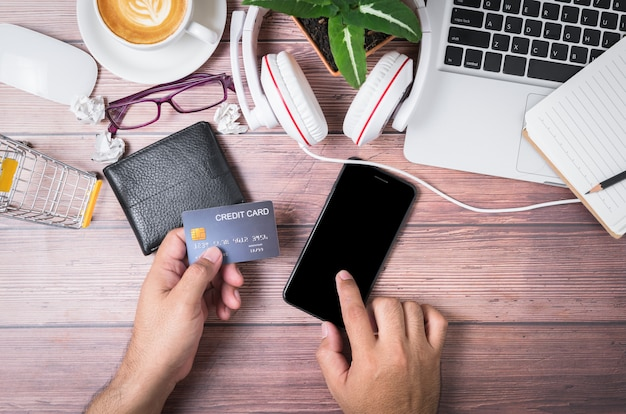 Man touch on black screen mobile phone and holding credit card on wallet Premium Photo
