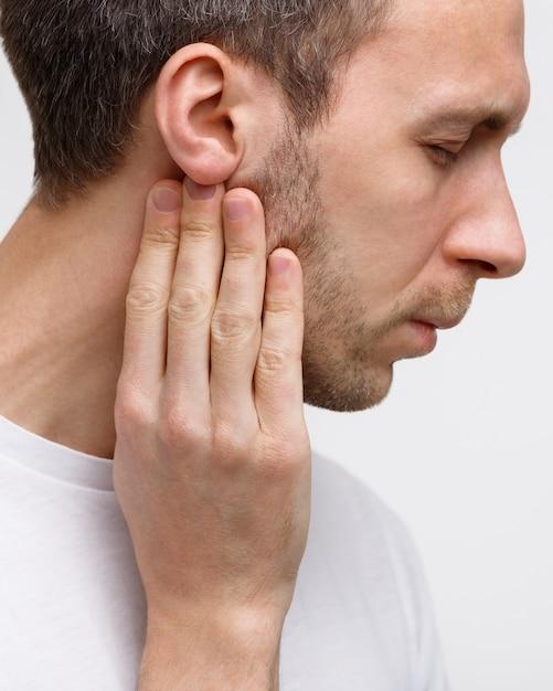 Мужчина касается лимфатических узлов пальцами возле уха Premium Фотографии