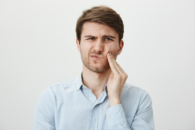 Man touching cheek and grimacing from pain from toothache, need dentist Free Photo