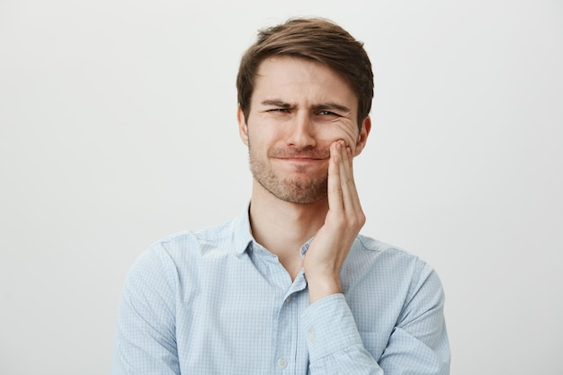 Man touching cheek and grimacing from pain from toothache Free Photo