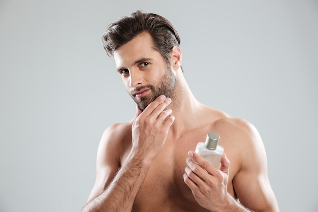 Man touching his face while holding bottle of perfume Free Photo