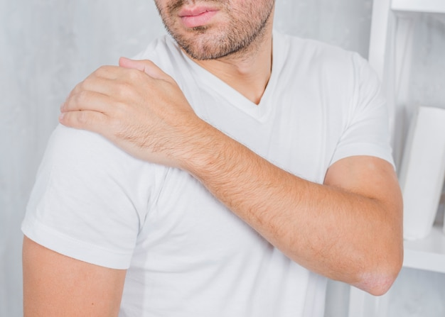 A man touching his injured shoulder with hand Free Photo
