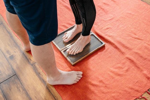 Мужчина-тренер помогает женщине стоять на доске садху-йоги, босиком на гвоздях Premium Фотографии