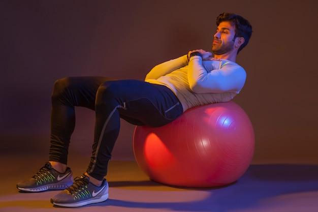 Man training on fitness ball Free Photo