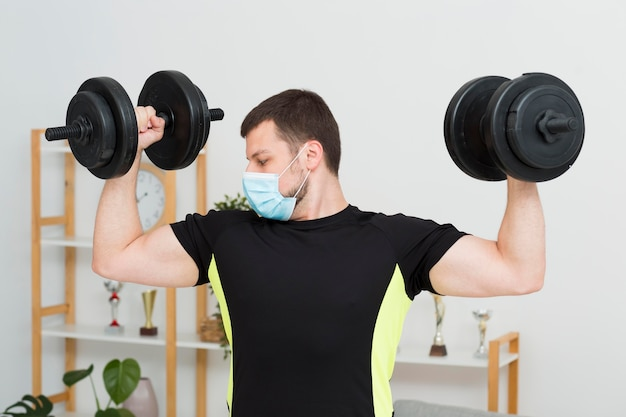 Man training at home while wearing a medical mask Free Photo