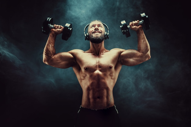 Man training muscles with dumbbells in studio on dark background with smoke. Premium Photo