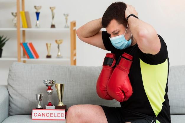 屋内で医療用マスクを着用しながらトレーニングする男性 無料写真