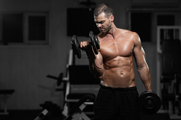 Man trains in the gym athletic man trains with dumbbells, pumping his biceps Premium Photo