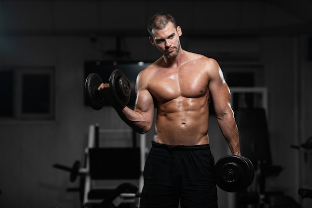 Man trains in the gym. athletic man trains with dumbbells, pumping his biceps Premium Photo