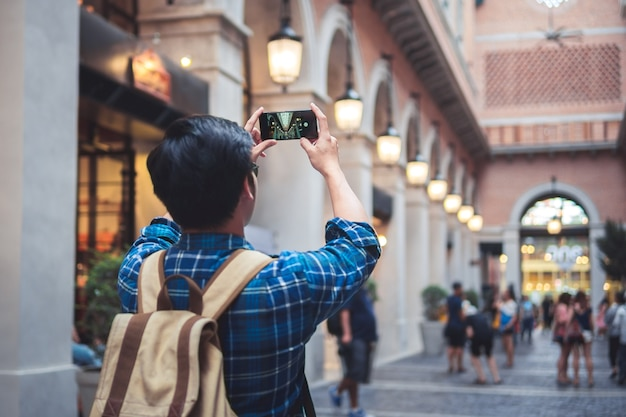 Man travel concept tourist taking photo by phone and put up hand overhead Premium Photo
