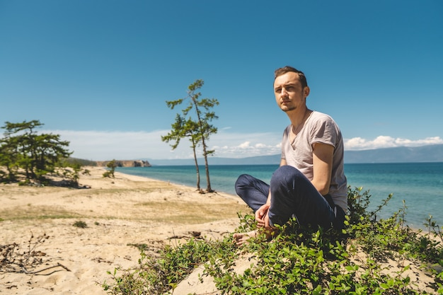 Man traveler relaxing on the beach of olkhon island overlooking the water of the lake and the mountains and the blue sky Premium Photo