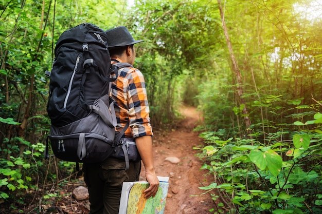 Man traveler with backpack and map in the forest Premium Photo
