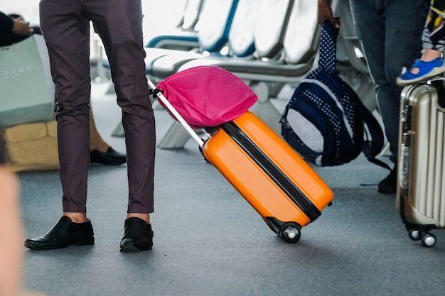 Man traveller with travel suitcase or luggage walking in airport terminal walkway Premium Photo