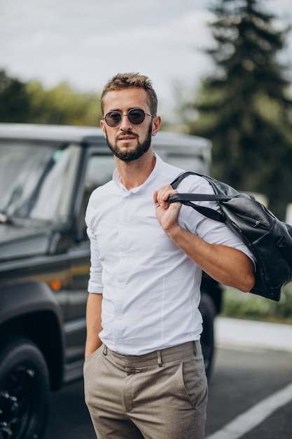 Man travelling with bag and standing by the car Free Photo