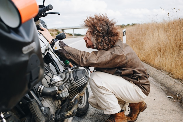 Man tries to fix motorbike on road side Free Photo