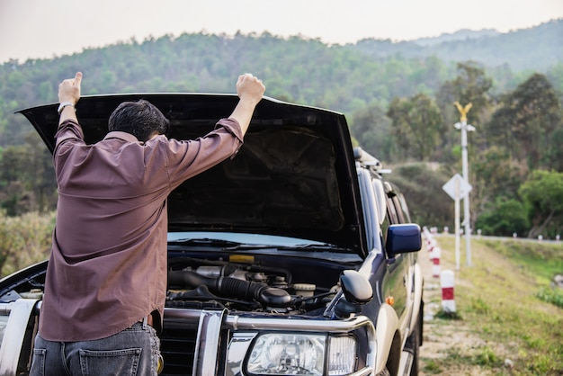 Man try to fix a car engine problem on a local road chiang mai thailand Free Photo