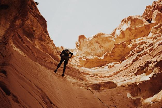 Uomo che cerca di scalare le scogliere del canyon Foto Gratuite