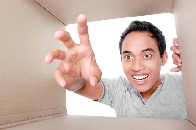 Man trying to take something inside box Premium Photo