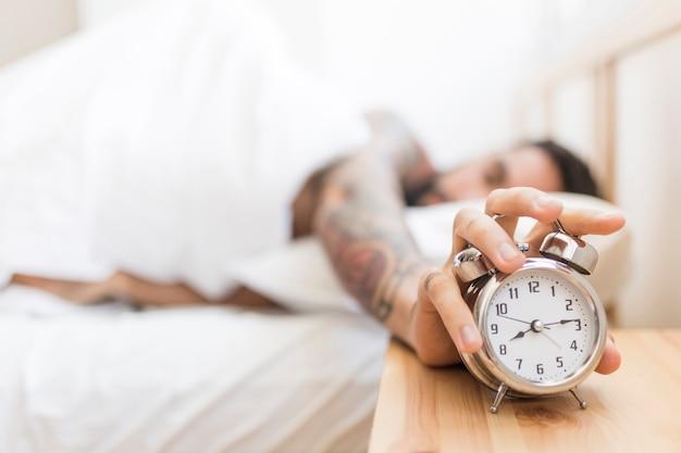 Man turning off alarm clock while lying on bed Free Photo
