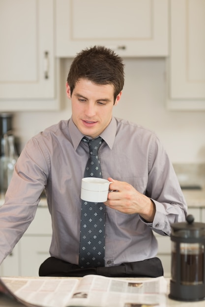 Man turning the page while drinking coffee Premium Photo