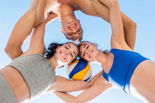 Un uomo e due donne in posa insieme alla pallavolo Foto Gratuite