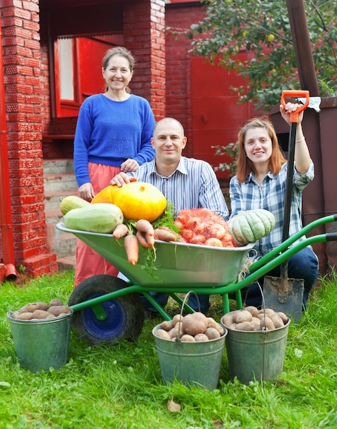Man and two women with  harvested vegetables Free Photo