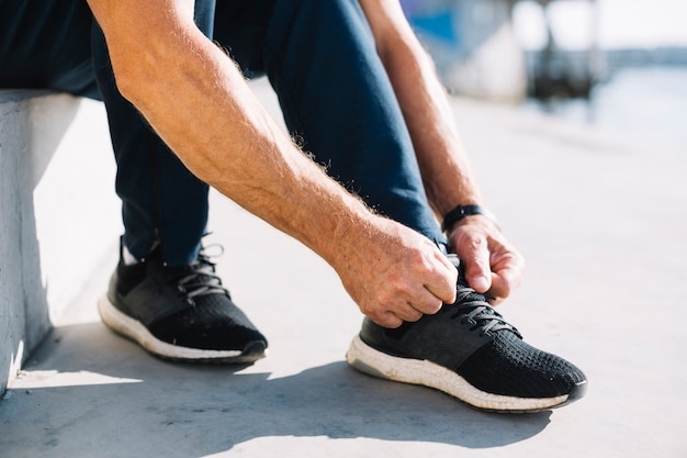 Man tying his left shoe laces Free Photo
