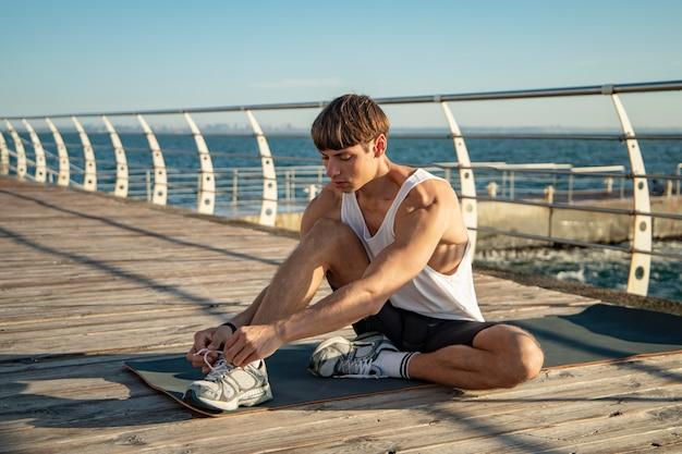Uomo che si allaccia i lacci delle scarpe in spiaggia prima di allenarsi Foto Gratuite