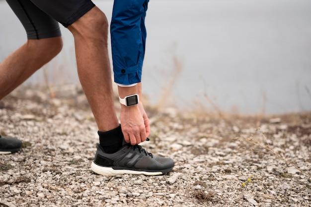 Мужчина завязывает шнурки на тропе Premium Фотографии
