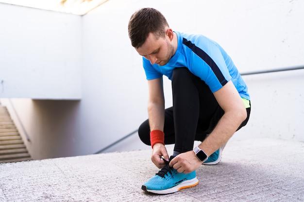 コンクリート背景に彼のスポーツの靴を結ぶ男 無料写真