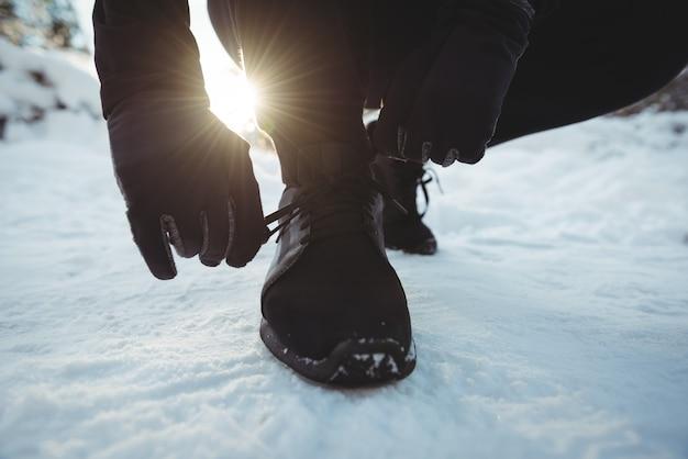 森の中で靴ひもを結ぶ男 無料写真