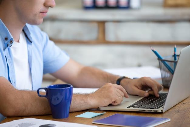 Man typing on a laptop Free Photo