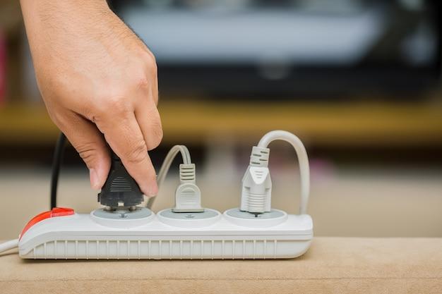 Man unplugged plug to save on energy Premium Photo