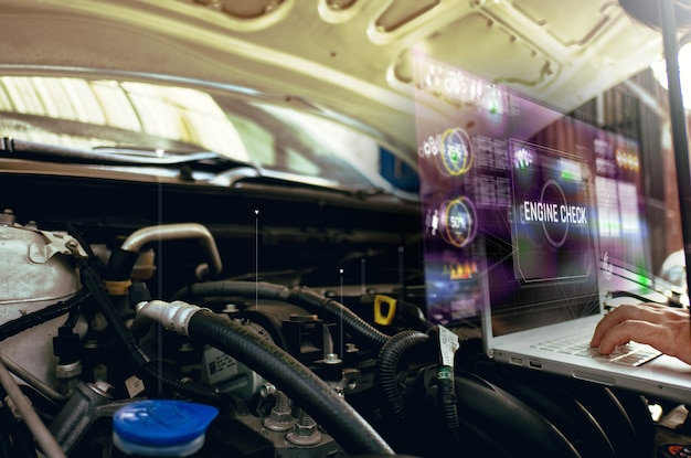 Man use laptop to analysis on his car engine with hologram. the concept of engine service hologram communication, network, insurance Premium Photo