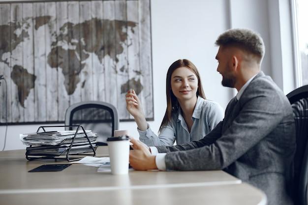 L'uomo usa una tavoletta. partner commerciali in una riunione d'affari le persone sono sedute al tavolo Foto Gratuite