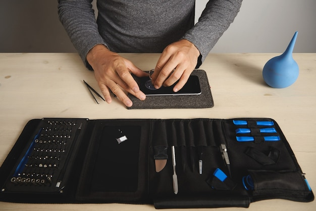 Man uses vacuum plug to remove screen from broken phone, his toolkit with special tools near Free Photo