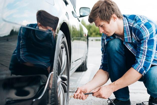 タイヤの空気ポンプを使用している人 Premium写真