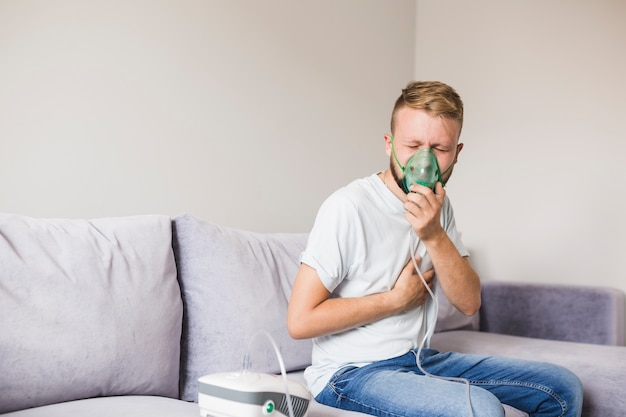 Man using asthma nebulizer holding hand on chest Free Photo