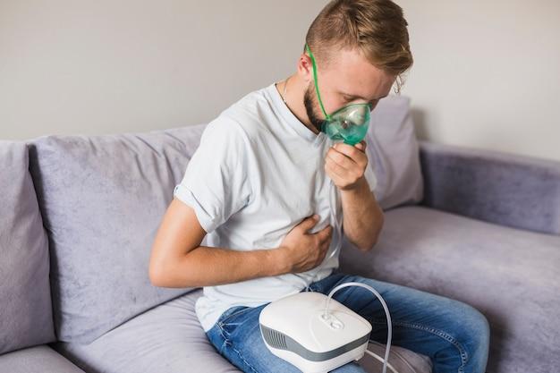 Man using asthma nebulizer at home Free Photo